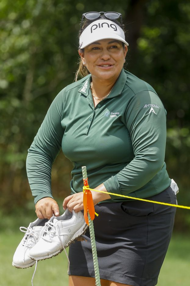 Professional golfer Lizette Salas smiles as she cleans off her muddy shoes at the No. 10 tee box during the second round of the LPGA VOA Classic on Friday, July 2, 2021, in The Colony, Texas. (Elias Valverde II/The Dallas Morning News)