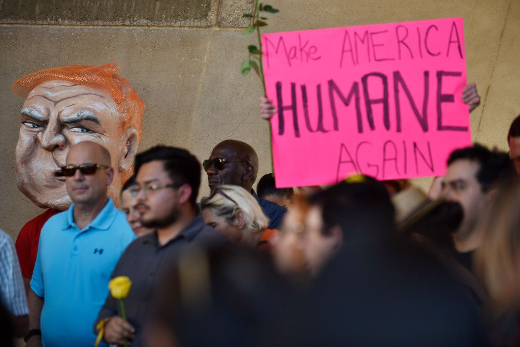 Immigration supporter Charles Hermes, far-left, wears a President Trump mask during a protest against the cruel and inhumane treatment of immigrants in the U.S., Thursday evening outside of City Hall in Dallas, June 14, 2018. The protest was conducted by local activists and the organization Families Belong Together. (Ben Torres/Special Contributor)
