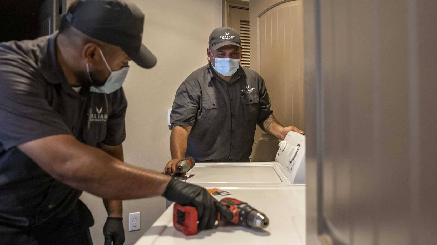 Valiant Residential lead maintenance technician Adrian Mendez (right) and assistant maintenance technician Rafael Muñoz work on washing machines at the Lakewood Flats Apartments in Dallas on Sept. 8.