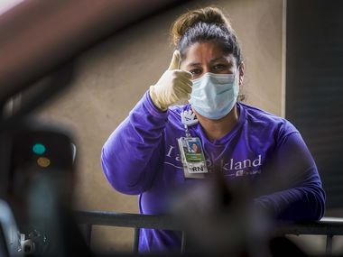 Parkland Homeless Outreach Medical Services (HOMES) program nurse manager Dolores Diaz gives thumbs up to a patient at a COVID-19 drive-through testing site at American Airlines Center on Monday, April 20, 2020, in Dallas.