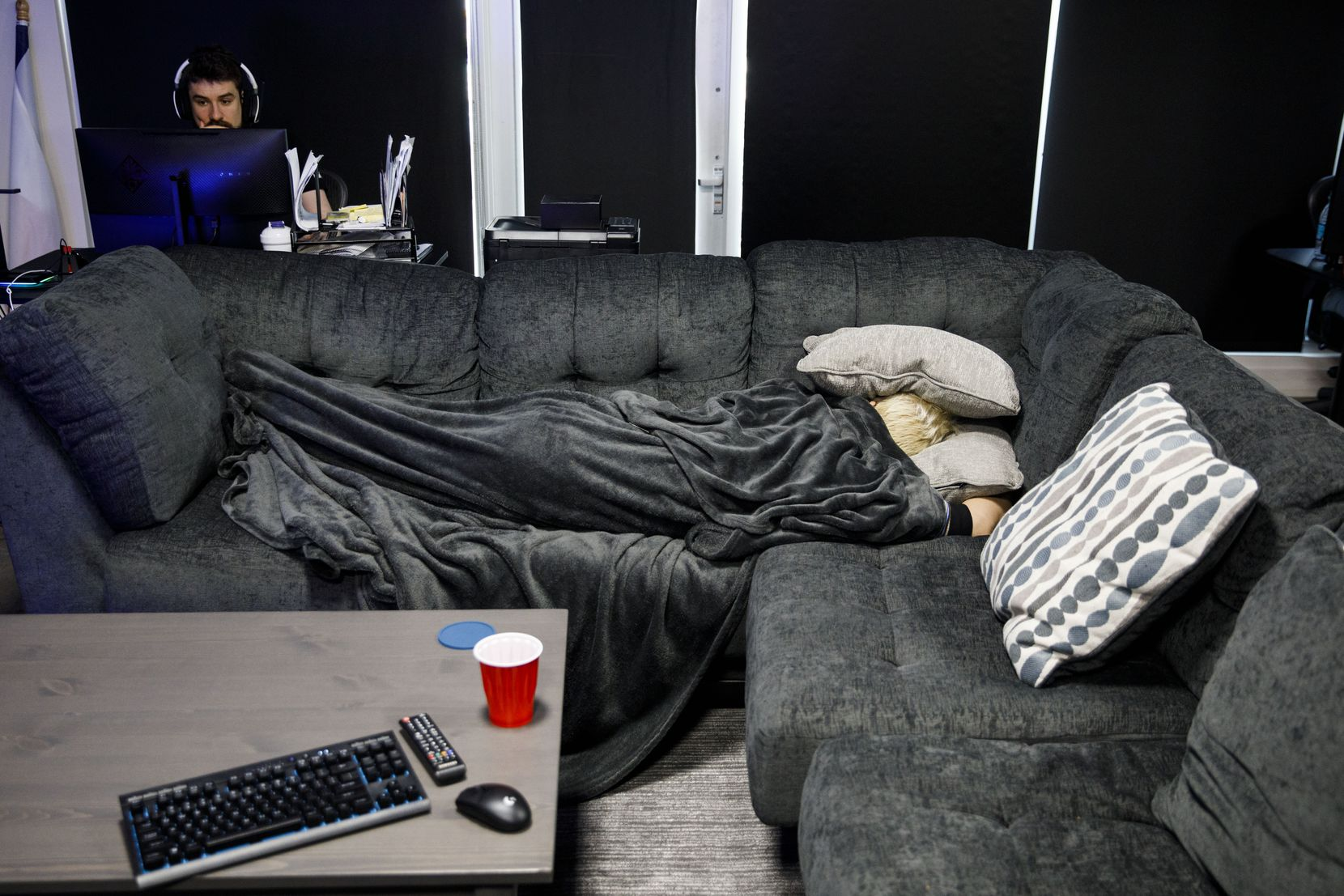 OGE takes a nap at the Dallas Fuel team facility in the Los Angeles area while general manager Mat Taylor sits at his computer.