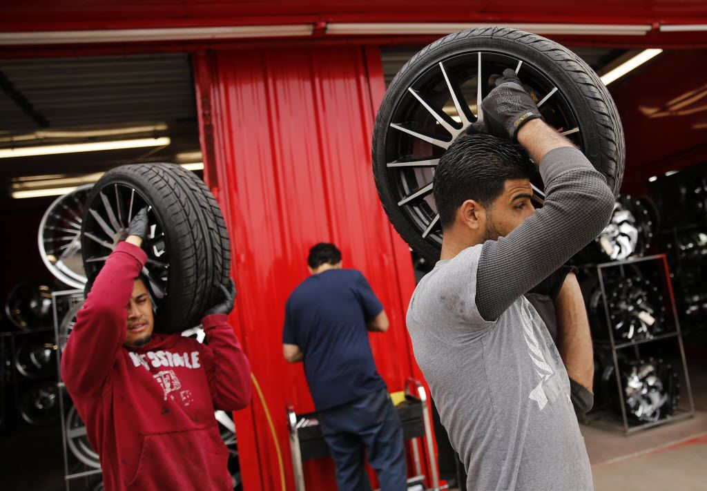 Danny Hossin (right) and Alex Ubaldo carry a set of tires to Mini Cooper after rebalancing them at Omar's Wheels and Tires, the Dallas tire shop targeted in 2015 by a gunman with a vendetta against Muslims.