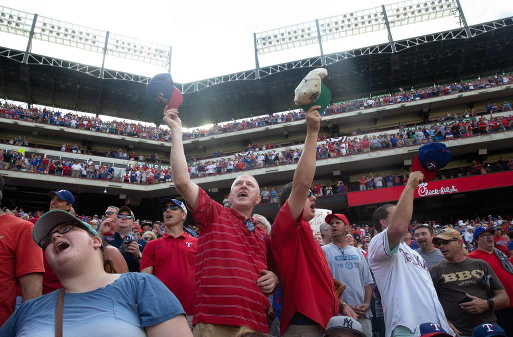 "Frank Targac (left) sings ""Take Me Out to the Ballgame"" with his son, Allen Targac (center) and Coby Cool (right) during the middle of the 7th inning during the Texas Rangers' final game ever played at Globe Life Park in Arlington, Texas, on Sunday, Sep. 29, 2019. Following the game, fans enjoyed a ceremony and parade to place home plate at the new, adjacent Globe Life Field."