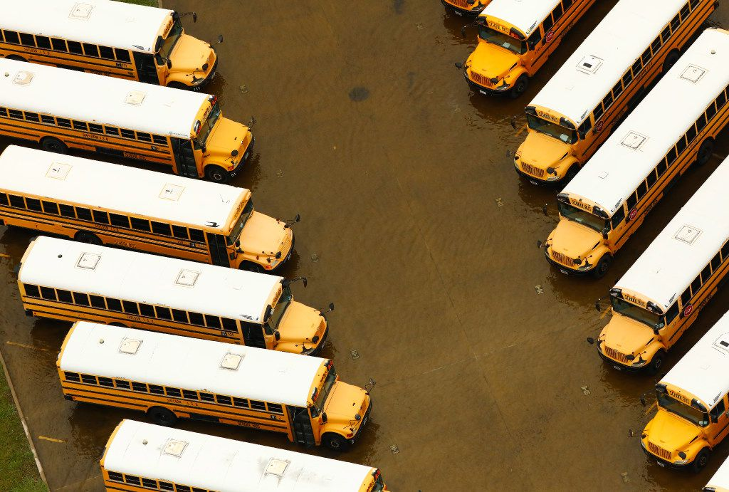 A yard full of school buses sit in receding flood water at Sheldon ISD near Houston, Texas, Wednesday, August 30, 2017. Hurricane Harvey inundated the Houston area with several feet of rain.