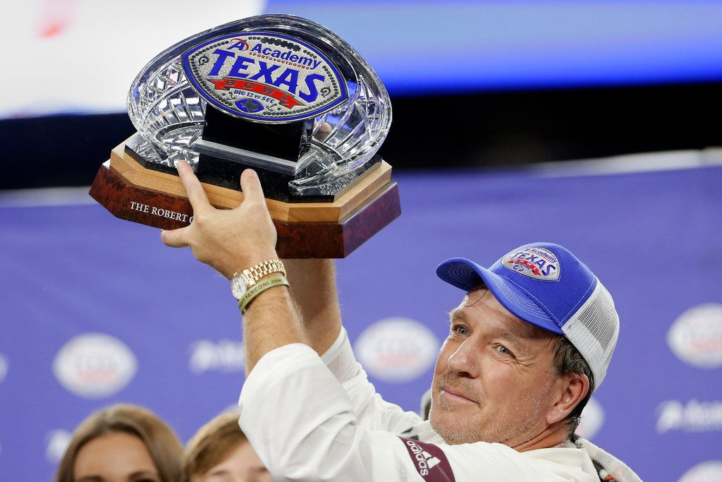 Texas A&M coach Jimbo Fisher holds up the Texas Bowl trophy after the team's 24-21 win over Oklahoma State in the NCAA college football game Friday, Dec. 27, 2019, in Houston. (AP Photo/Michael Wyke)