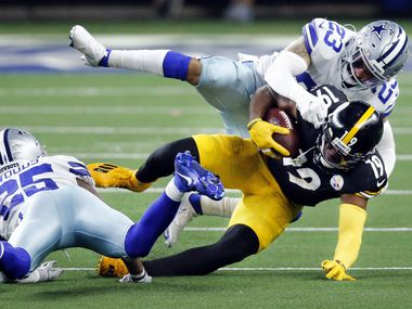 Steelers wide receiver JuJu Smith-Schuster (19) is taken down by Cowboys safeties Darian Thompson (23) and Xavier Woods (25) during the third quarter of a game at AT&T Stadium in Arlington on Sunday, Nov. 8, 2020.