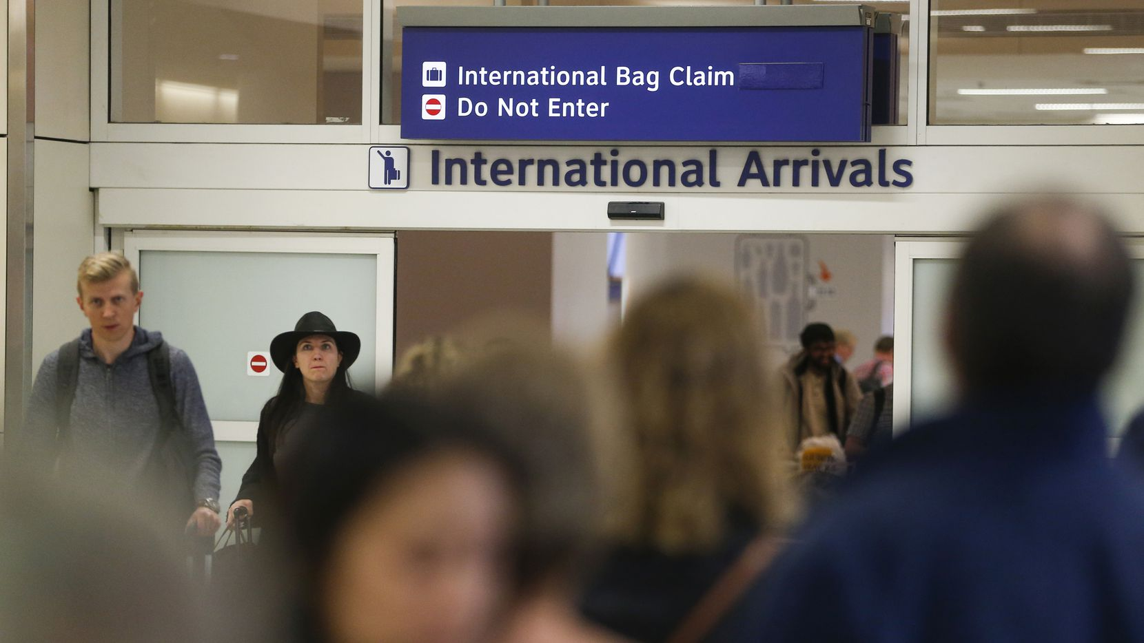 Travelers, some seen wearing protective masks, arrive in the international arrivals area of DFW International Airport on Tuesday, Jan. 28, 2020. DFW suspended all direct flights to and from China last week according to a DFW press release.