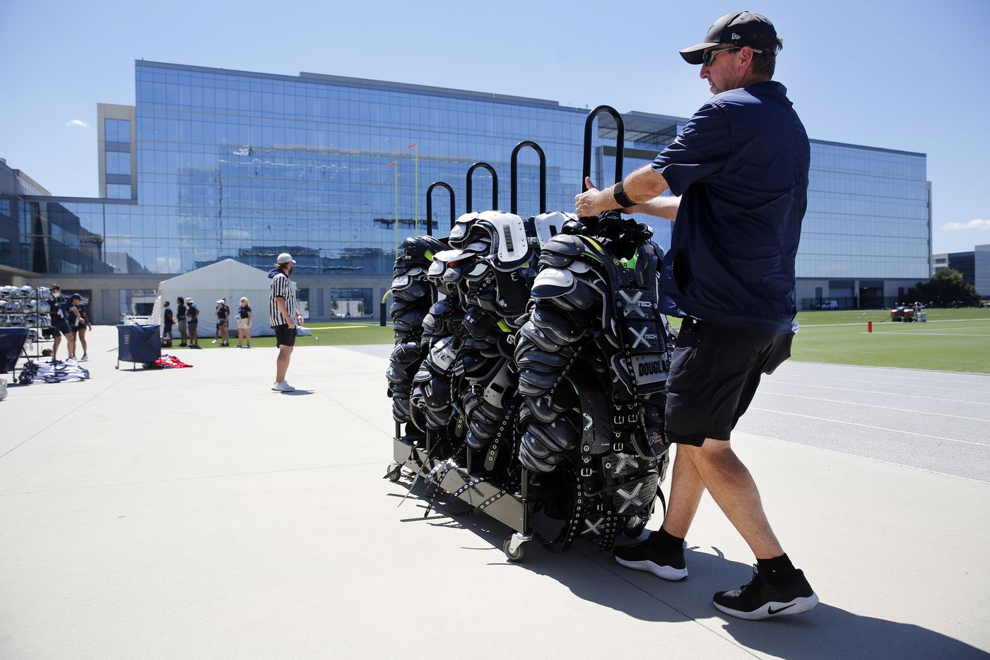 Dallas Cowboys equipment manager Mike McCord pulls a rack of shoulder pads after players shed them following Training Camp practice at The Star in Frisco, Texas, Tuesday, August 24, 2021.(Tom Fox/The Dallas Morning News)