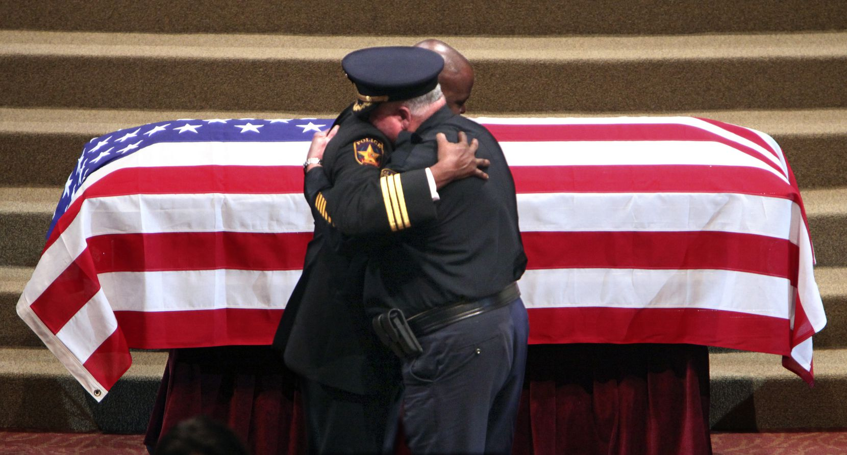 Lancaster Police Chief Keith Humphrey (left) and assistant chief Larry Flatt embraced at the conclusion of funeral services for Lancaster police Officer Craig Shaw at the Inspiring Body of Christ Church in Dallas in June 2010. Officer Shaw was shot and killed by David Brown Jr., son of Dallas Police Chief David Brown.