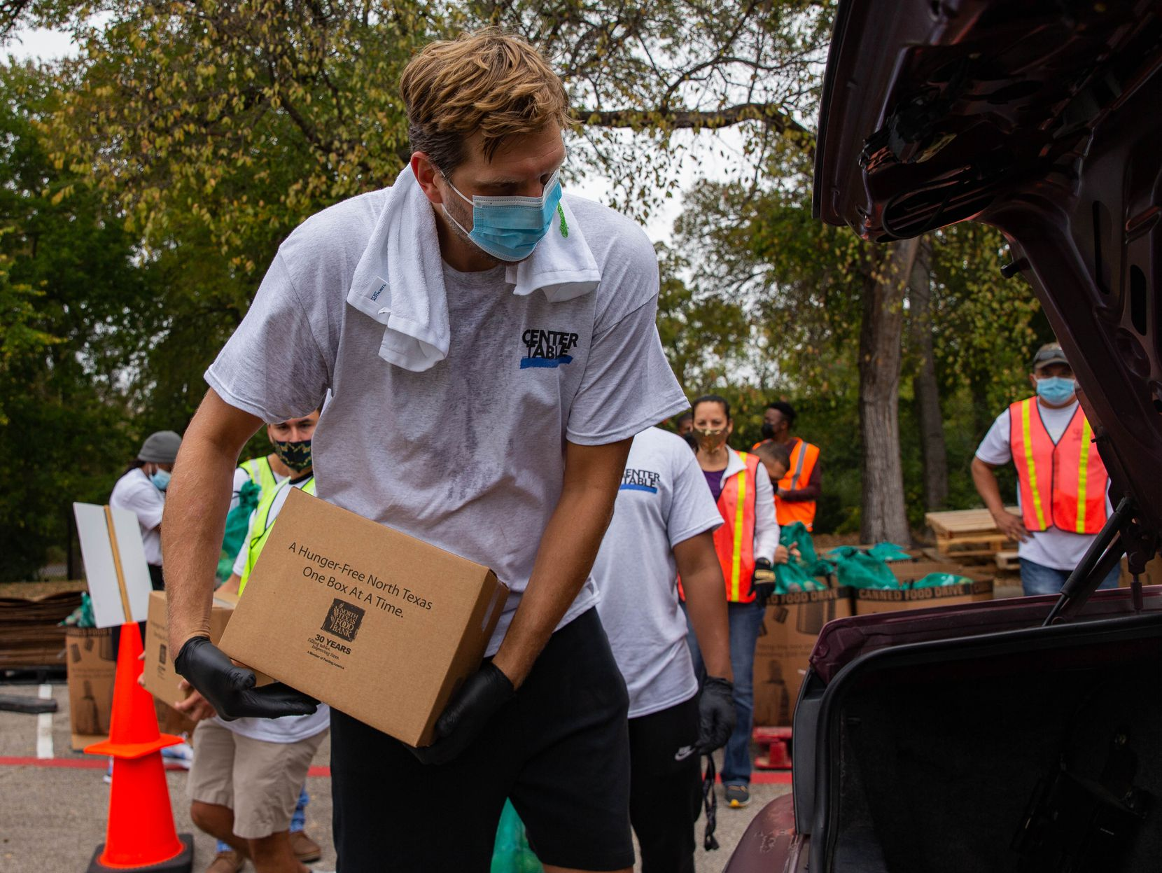 Former Dallas Mavericks player Dirk Nowitzki (left) loads a car during the Center Table Fall Harvest food drive at the Mark Cuban Center in Dallas on Thursday, Oct. 22, 2020.