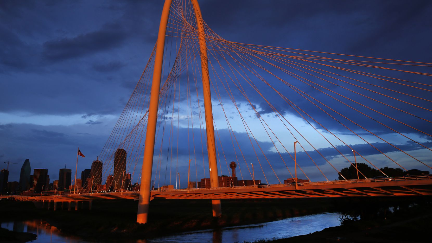 The setting sun illuminates the Margaret Hunt Hill Bridge and downtown Dallas after thunderstorms rolled through the middle of the Metroplex on July 10, 2019.