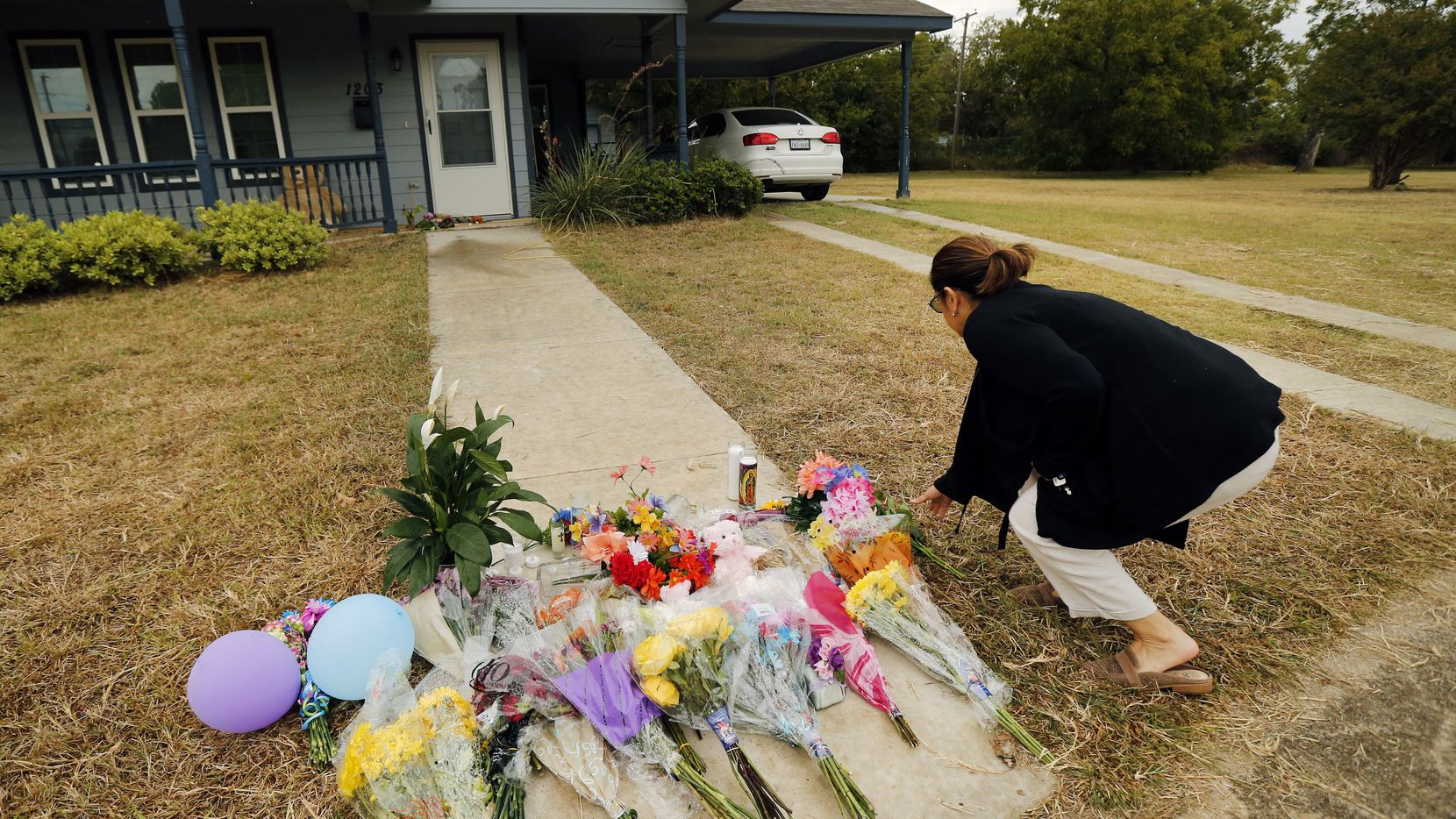Anastasia Gonzalez of Burleson, Texas leaves a flowers on the front sidewalk of Atatiana Jefferson's home on E. Allen Ave in Fort Worth. In the wake of Fort Worth officer Aaron Dean shooting and killing Jefferson in her home, people have been leaving flowers at a memorial.  (Tom Fox/The Dallas Morning News)
