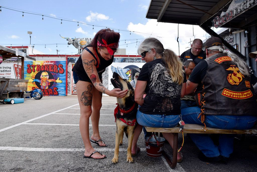 Elysia Edwards (left), 35, of Dallas meets a dog named Raine and her owner, Carrie Oliver, as the group of people eat and drink outside in the patio area of Strokers Dallas on Saturday afternoon, June 16, 2018.