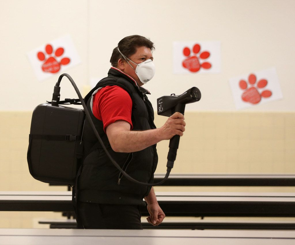 Julian Cruz, a custodian with Garland ISD, sprays a disinfectant in the cafeteria at Parkcrest Elementary School in Garland on Feb. 8.