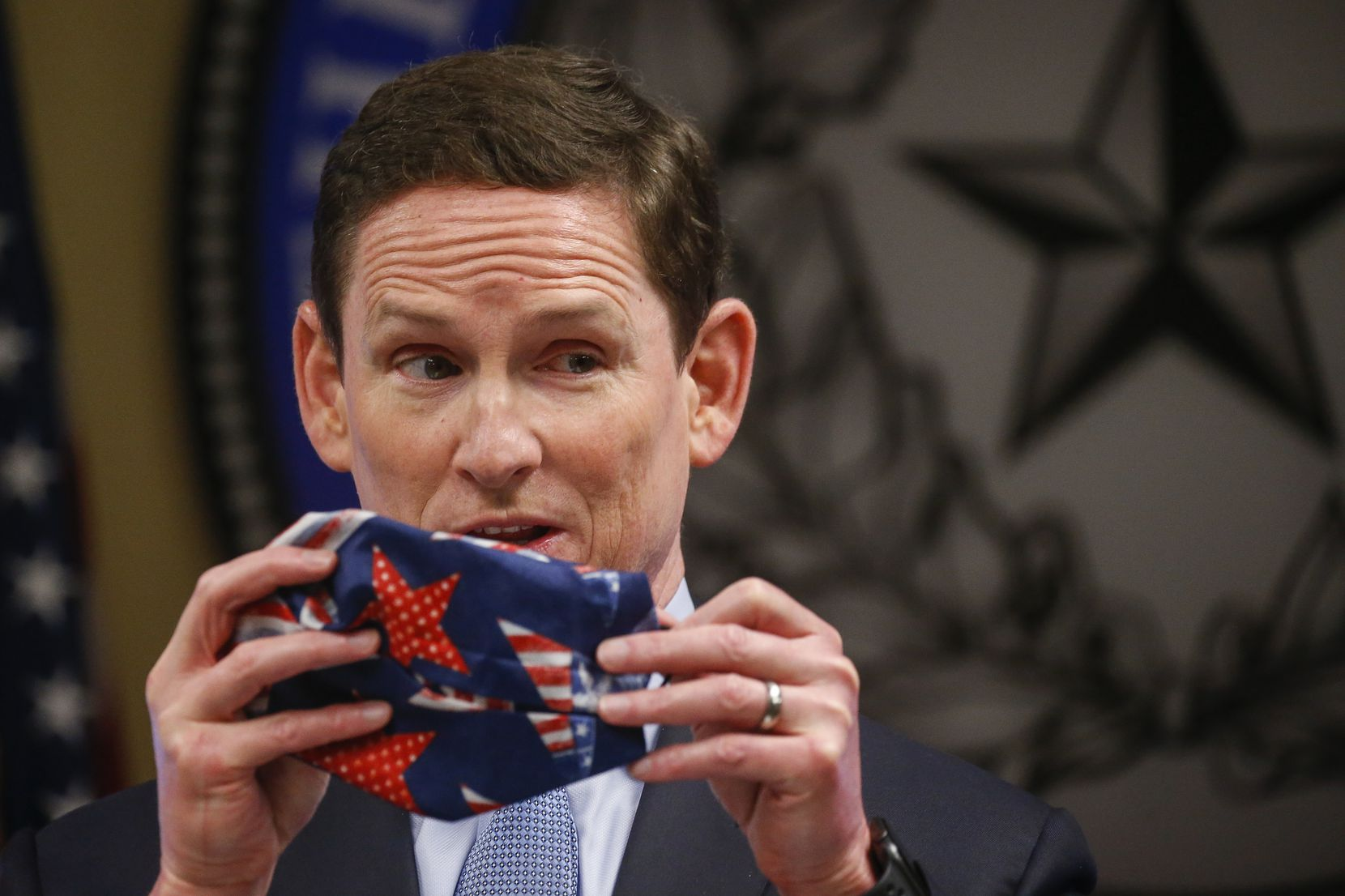 Dallas County Judge Clay Jenkins displays an improvised cloth face mask made with a bandana and hair ties as he addresses members of the media regarding the new coronavirus pandemic on Wednesday, April 8, 2020 at the Dallas County Emergency Operations Center in Dallas.