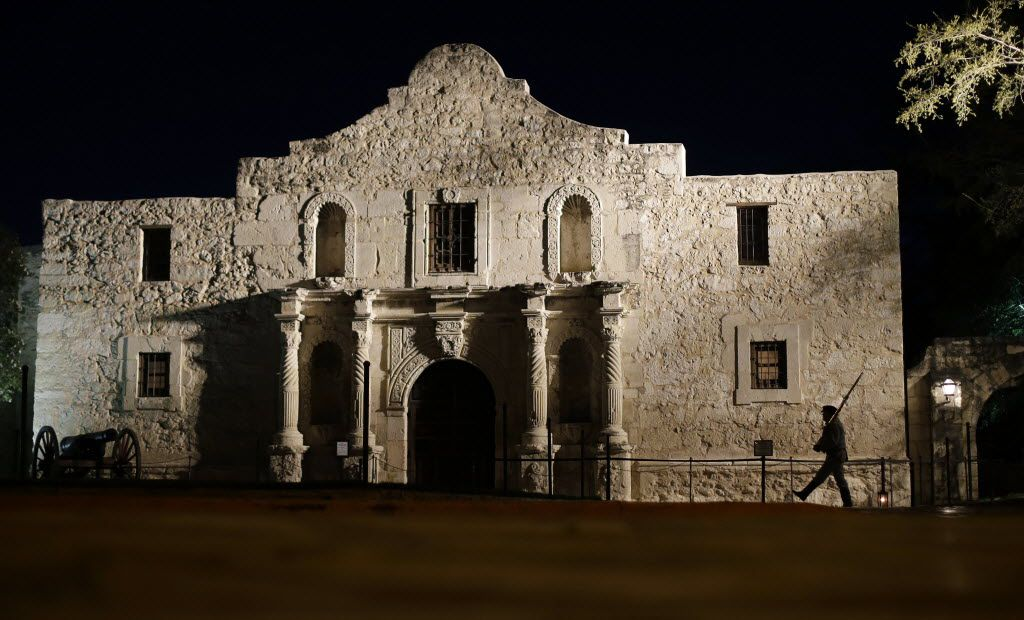 In this March 6, 2013, file photo, John Potter, a member of the San Antonio Living History Association, patrols the Alamo in San Antonio, during a pre-dawn memorial ceremony to remember the 1836 Battle of the Alamo and those who fell on both sides.