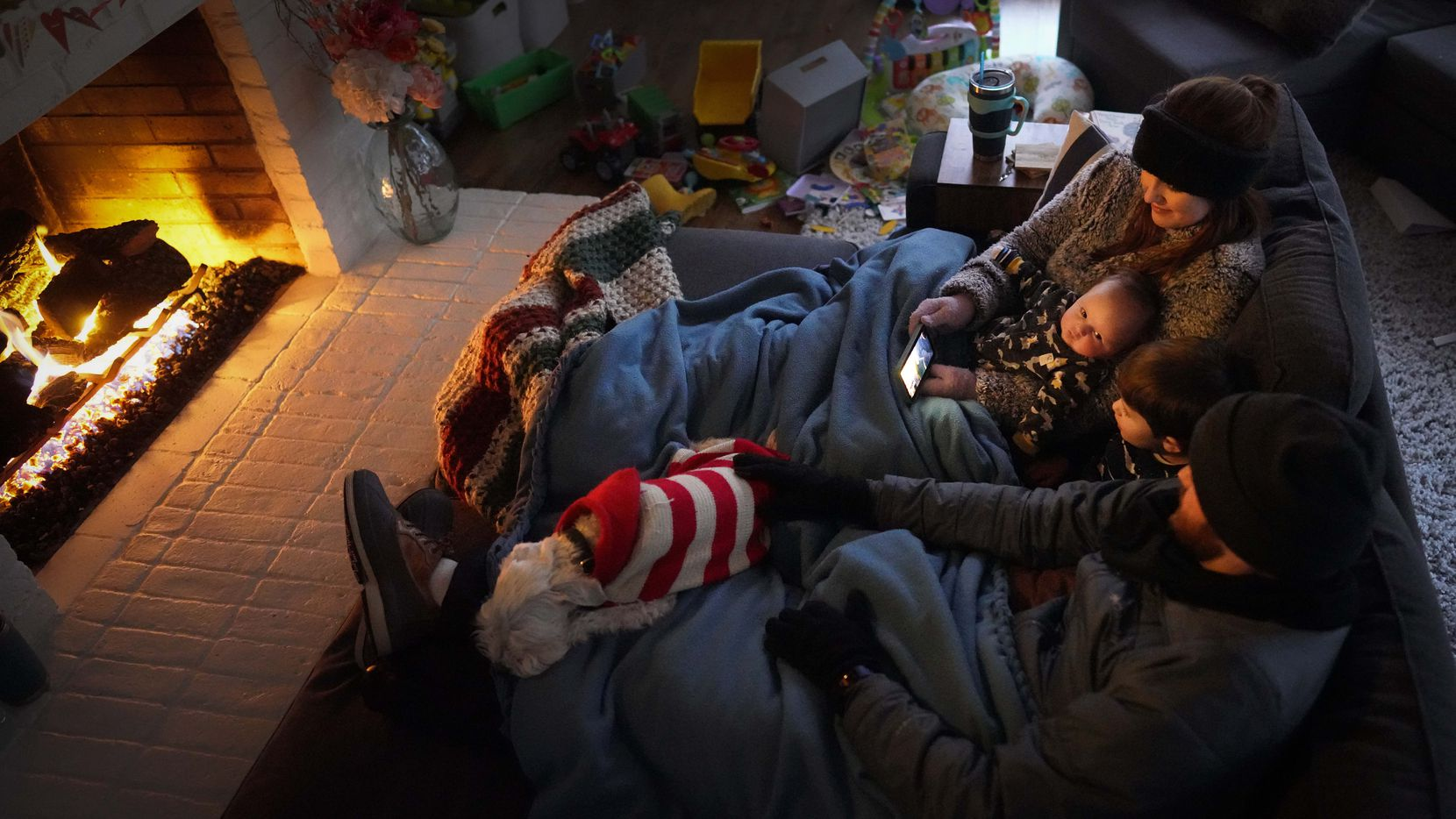 Dan Bryant and his wife Anna huddle by the fire with sons Benny, 3, and Sam, 12 weeks, along with their dog Joey, also wearing two doggie sweaters, with power out and temperatures dropping inside their home after a winter storm brought snow and freezing temperatures to North Texas on Monday.