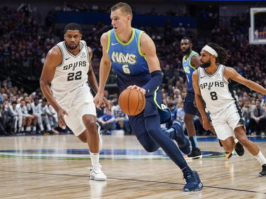 Dallas Mavericks forward Kristaps Porzingis (6) brings the ball up the court past San Antonio Spurs forward Rudy Gay (22) and guard Patty Mills (8) during the second half of an NBA basketball game at American Airlines Center on Thursday, Dec. 26, 2019, in Dallas.