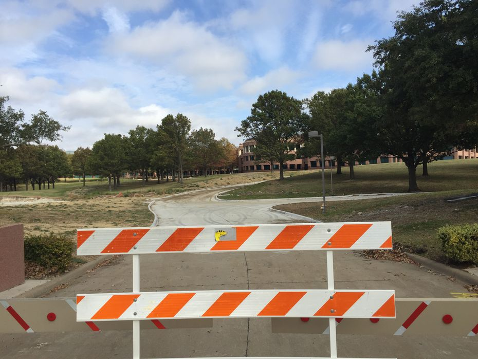 A barricade is in the long driveway to what was the main entrance of J.C. Penney's headquarters at 6501 Legacy Drive in Plano.