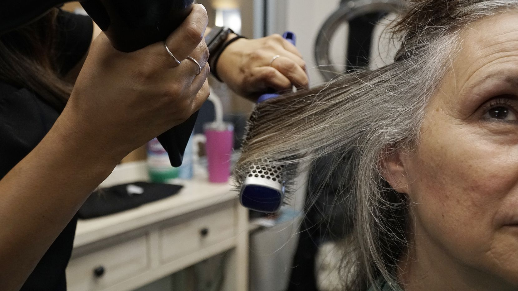 Hairstylist Veronica Vazquez of Sola Salons in Colleyville helped ease Harriet Blake's transition to gray hair. Going gray is nature's way of nudging people into maturity, Blake says.
