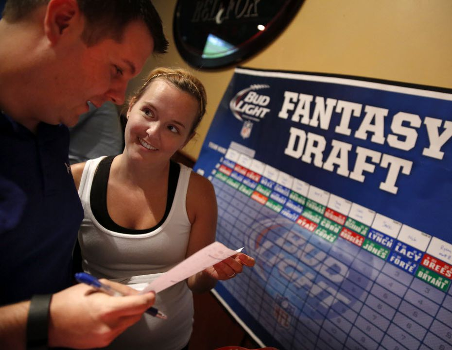 Top 100 ONLY  Evantage Inc president Chris Auwarter (left) makes his third round pick in the company Fantasy Football Draft at the Fox and Hound in Dallas as his wife wife Laura Auwater (right) coordinates. (Tom Fox/The Dallas Morning News)