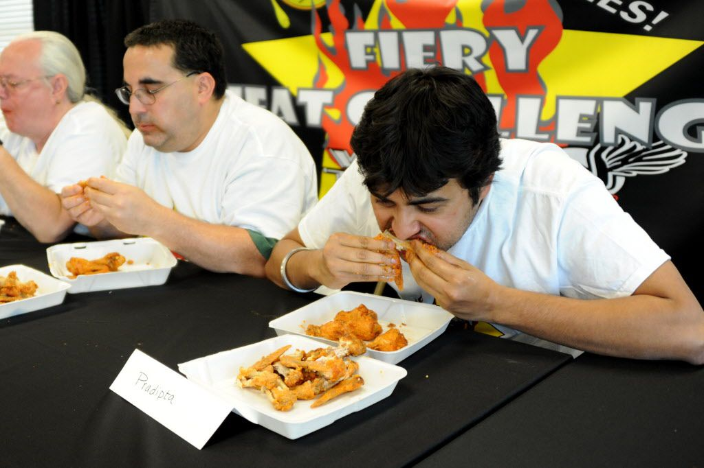 Pradipta Chattejee chows down on wings by Wing Town at the Taste of Irving Fiery Heat Challenge in Irving, TX on May 16, 2015.