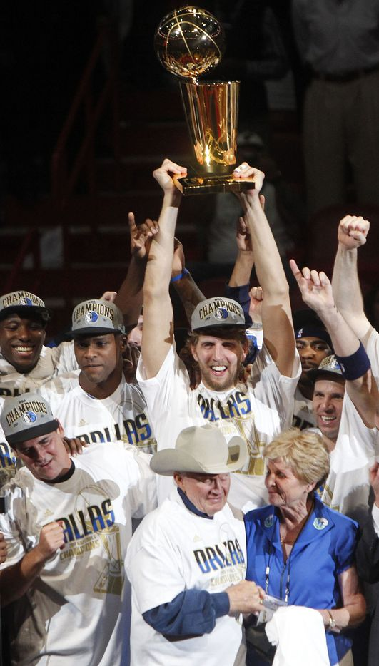 The Dallas Mavericks celebrate with the trophy after winning game six of the NBA Finals between the Miami Heat and the Dallas Mavericks at the American Airlines Arena in Miami, Florida, June 12, 2011. The Mavericks won 105-95 to take the title. At front in cowboy hat is the original Dallas Mavericks founding owner Don Carter. Dirk Nowitzki is holding the Larry O'Brien NBA Championship trophy.