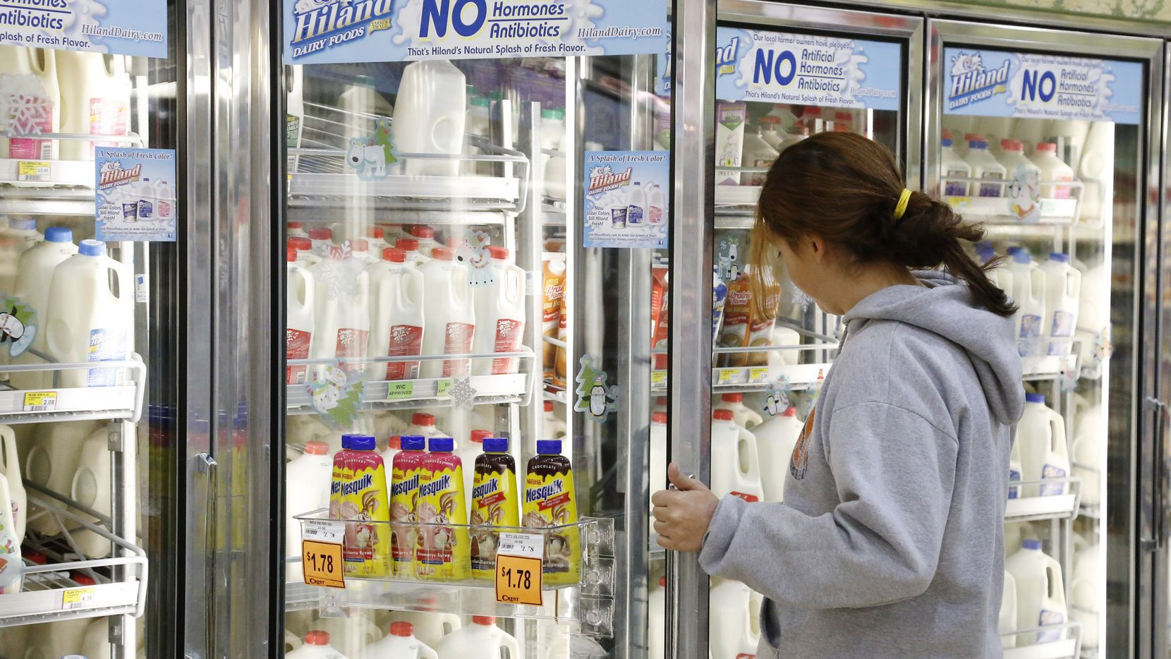 FILE - In this Dec. 4, 2013, file photo Jessica Walton, of Guthrie, Okla., reaches for a container of milk at a grocery store in Edmond, Okla. On Tuesday, Nov. 12, 2019, Dean Foods, the nation's largest milk processor, filed for Chapter 11 bankruptcy protection and said it may sell the company off to the Dairy Farmers of America. (AP Photo/Sue Ogrocki, File)