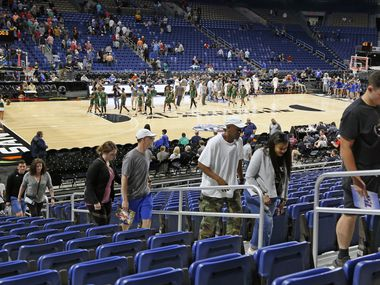 At the conclusion of the second Class 3A state semifinal, fans depart the Alamodome in San Antonio after the remainder of the UIL boys basketball state tournament was suspended March 12.