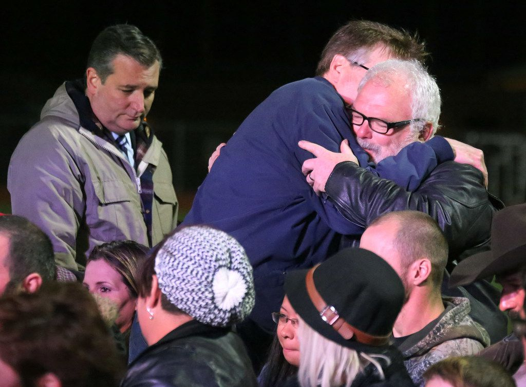 Texas Lt. Gov. Dan Patrick embraces hero Stephen Willeford, who shot and chased the gunman who attacked First Baptist Church of  Sutherland Springs. Senator Ted Cruz stands by at a memorial service at the Floresville High School football stadium in Floresville, Texas. Photographed on Wednesday, November 8, 2017.