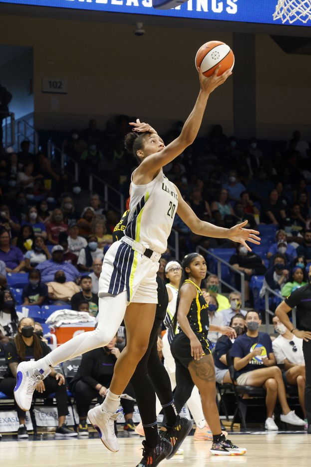 Dallas Wings forward Isabelle Harrison (20) makes a basket as she is brushed not he head by Los Angeles Sparks center Amanda Zahui B,  during the second half of a WNBA basketball game in Arlington, Texas on Sunday, Sept. 19, 2021. (Michael Ainsworth/Special Contributor)