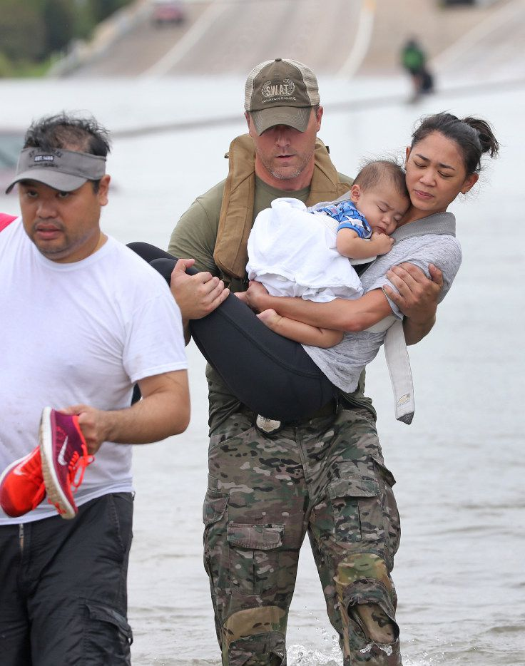Houston SWAT Officer Daryl Hudeck carries Catherine Pham and her 13-month-old son, Aidan, to safety after they were rescued by boat from the flooding on Interstate 610 south in Houston on Aug. 27, 2017. Catherine's husband, Troy Pham, is at left.