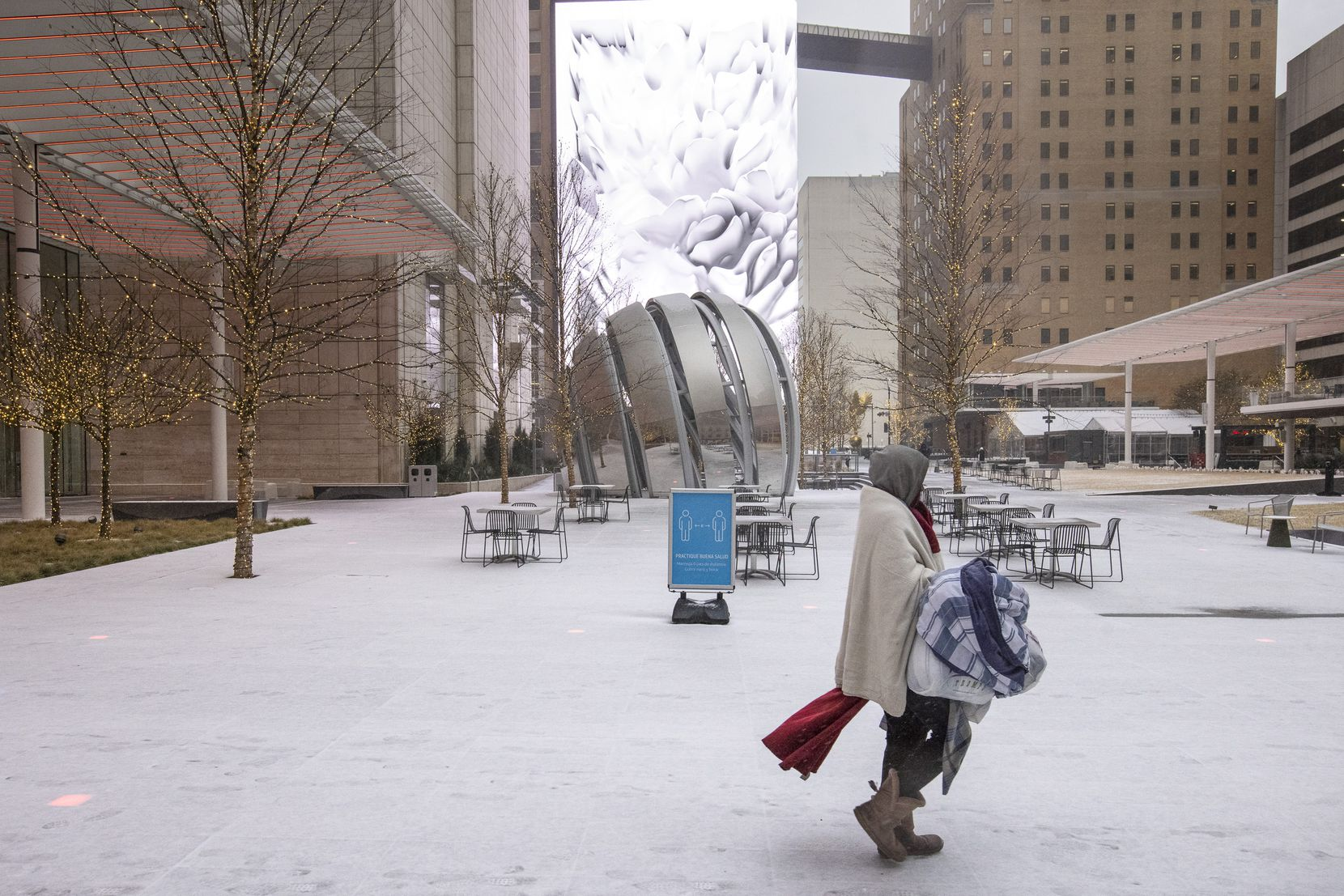 A person walks through snow past AT&T Discovery District in Downtown Dallas on Sunday, Feb. 14, 2021. The region is currently under a winter storm warning.