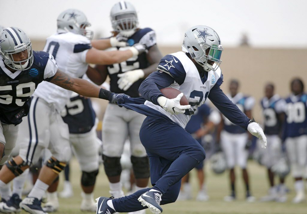 Dallas Cowboys middle linebacker Anthony Hitchens (59) grabs the shirt of Dallas Cowboys running back Ezekiel Elliott (21) as he makes his way up the field during the afternoon practice at training camp in Oxnard, California on Sunday, July 30, 2017. (Vernon Bryant/The Dallas Morning News)