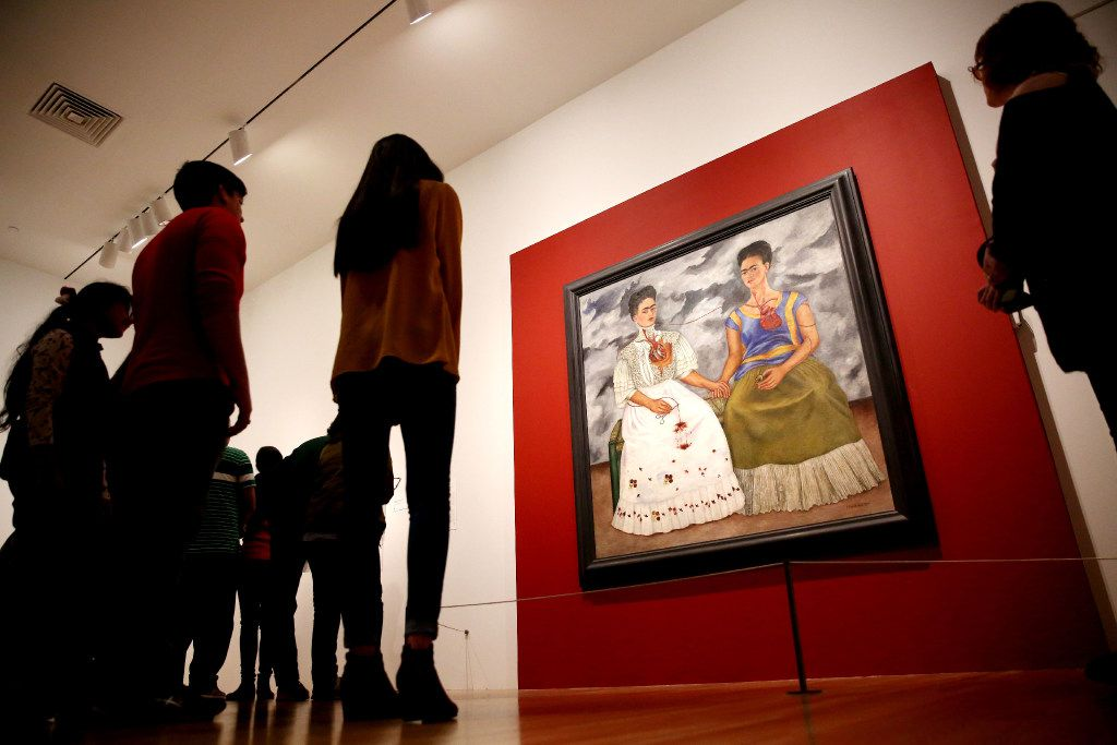 "A crowd gathers to look at ""The Two Fridas"" by Frida Kahlo in the ""Mexico 1900-1950: Diego Rivera, Frida Kahlo, Jose Clemente Orozco, and the Avant-Garde"" exhibit at the Dallas Museum of Art"