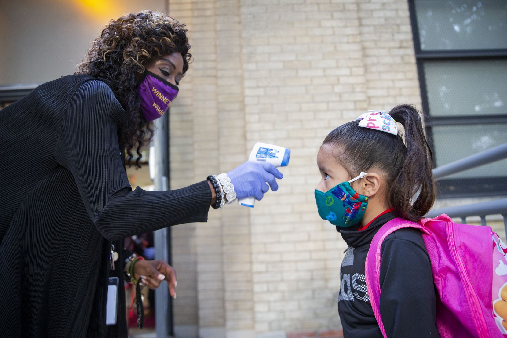 Assistant principal Clara Daniels checked Riley Pereyda's temperature at Winnetka Elementary in Dallas on Sept. 28, when students were allowed to begin in-person classes after several weeks of virtual learning.