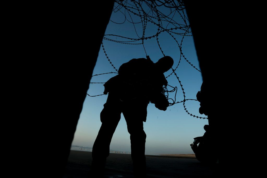 A Border Patrol officer fixes barbed wire at the beach on the U.S. side of the fence between San Diego, Calif., and Tijuana, Mexico.