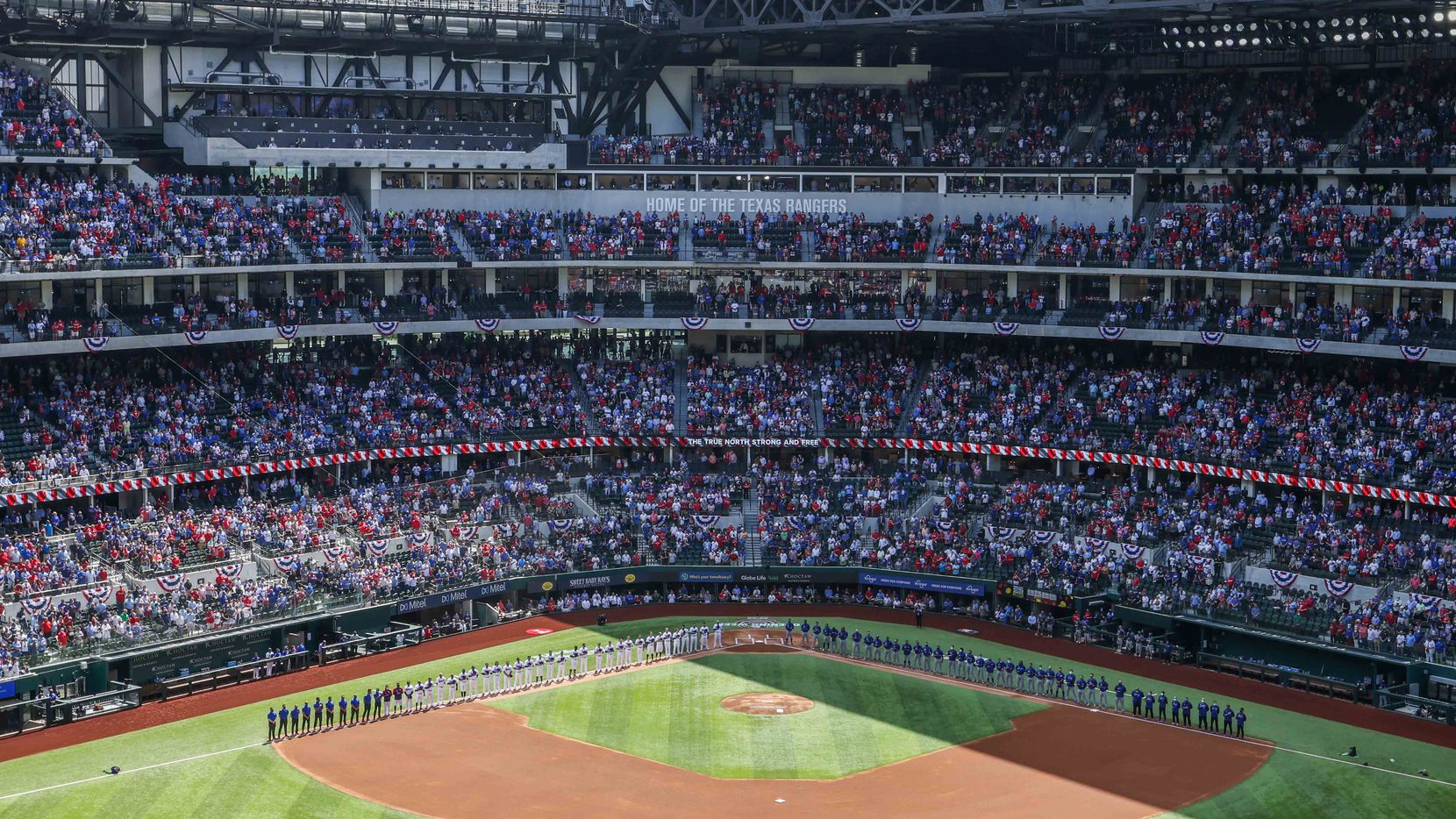 Texas Rangers and Toronto Blue Jays teams line up during the national anthem at the Globe Life Field during opening day in Arlington, Texas on Monday, April 5, 2021. (Lola Gomez/The Dallas Morning News)