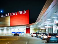 Cars pull up to the lightly trafficked departures curbside in front of Dallas Love Field airport on Friday, March 20, 2020, in Dallas.