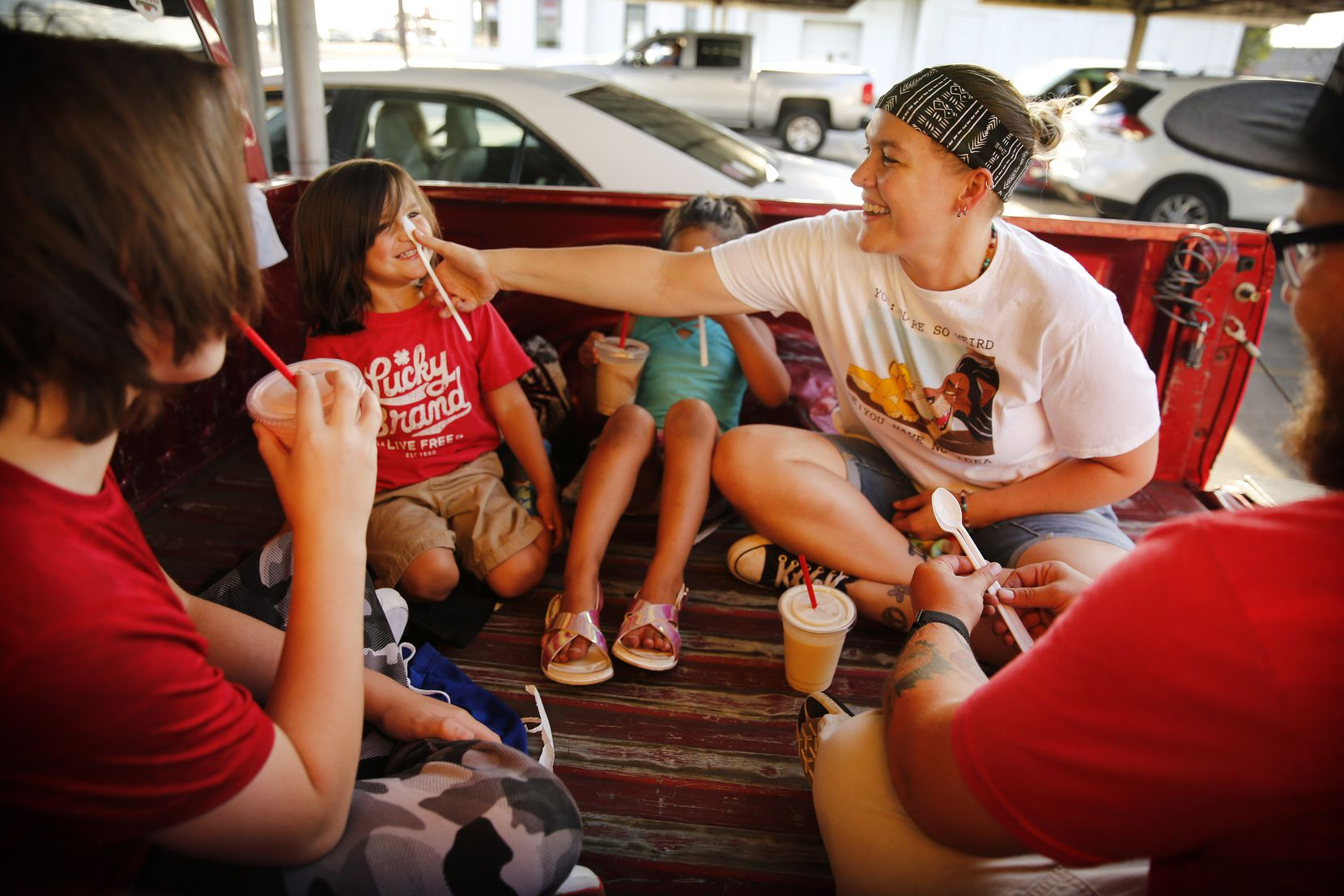 Erin Molina (facing, right) shows her son Ian Molina, 4, how to balance a spoon on his nose as they and her friend Logan Williams (right) and his younger brother Colt Turner (left) enjoyed shakes in the bed of their pickup at Keller's Drive-In on Northwest Highway in Dallas, Thursday, May 14, 2020. (Tom Fox/The Dallas Morning News)