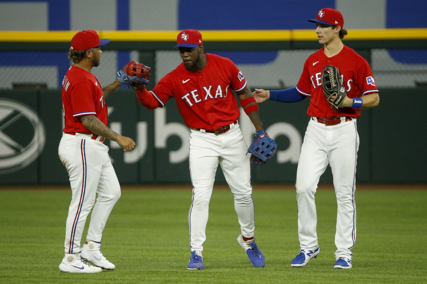 From left, Texas Rangers left fielder Willie Calhoun (5), Texas Rangers center fielder Adolis Garcia (53) and Texas Rangers right fielder Eli White (41) celebrate a 9-4 win over the Kansas City Royals at Globe Life Field on Friday, June 25, 2021, in Arlington. (Elias Valverde II/The Dallas Morning News)