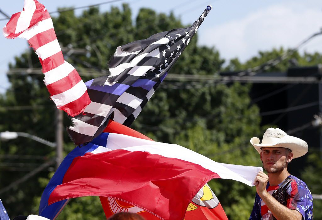 Counter protester Conner McCasland holds a flag across a Black Live Matter rally on Park Lane in Dallas, Sunday, July 10, 2016. (Jae S. Lee/The Dallas Morning News)