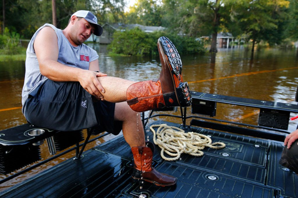 Kurt Rogers from Grapevine, Texas, empties out his boot while helping people out on boats after Hurricane Harvey near Vidor, Texas, on Sept. 3, 2017.