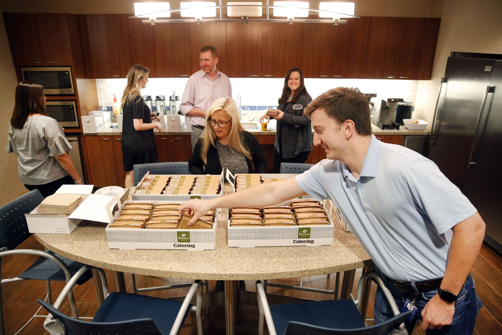 James Farrell, a senior benefits analyst, reaches for breakfast during an employee appreciation day in Lockton Dunning Benefits office in downtown Dallas.
