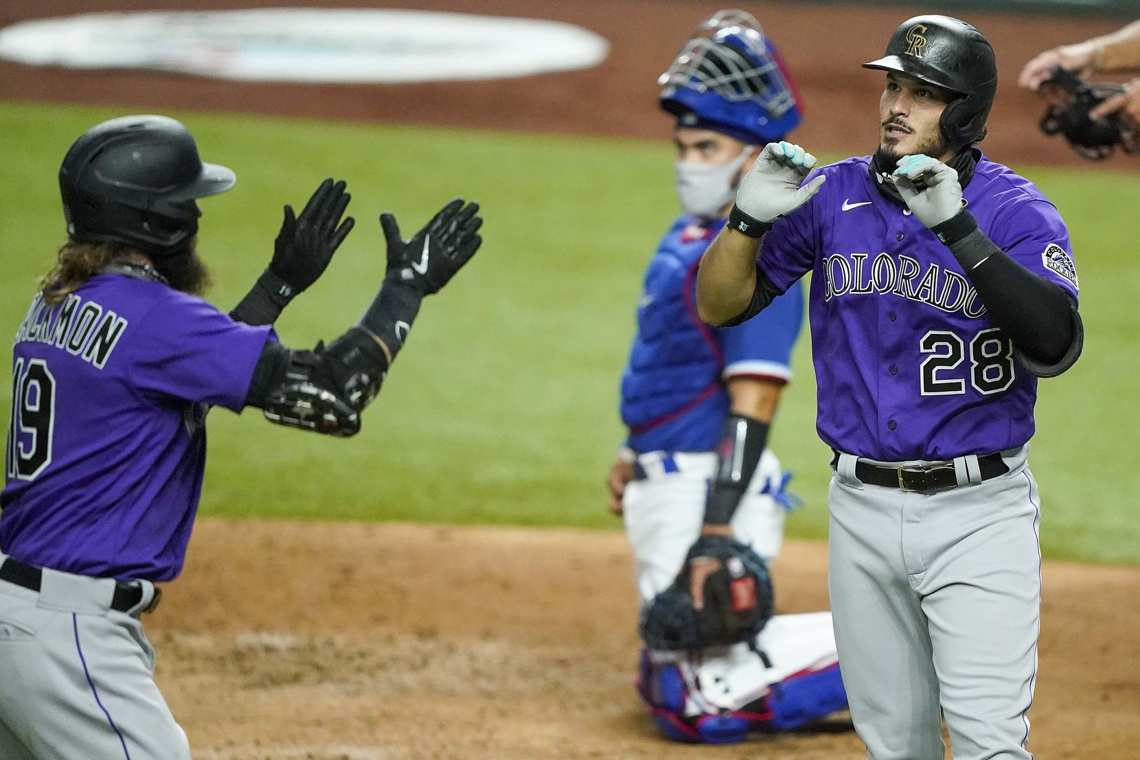 Texas Rangers catcher Robinson Chirinos watches Colorado Rockies third baseman Nolan Arenado (28) celebrate with outfielder Charlie Blackmon after hitting a 2-run home run during the fourth inning of an exhibition game at Globe Life Field on Tuesday, July 21, 2020.