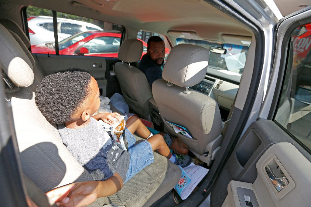 Attorney Lee Merritt (top) tells his 7-year-old son Stacy Merritt, Jr., have a seatbelt on as they leave for the Orthodontic office in Allen.