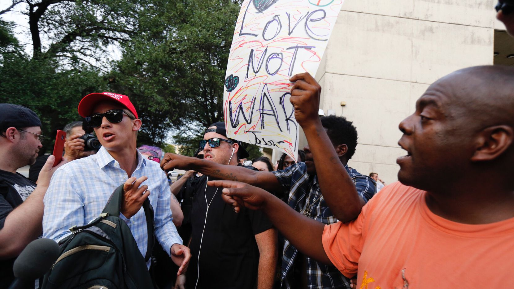 Kenyan Mark Wagema of Dallas (right) confronts a Trump supporter who chose not to identify himself  before the March Against White Supremacy rally at Pioneer Park Cemetery in downtown Dallas, Saturday, August 19, 2017.
