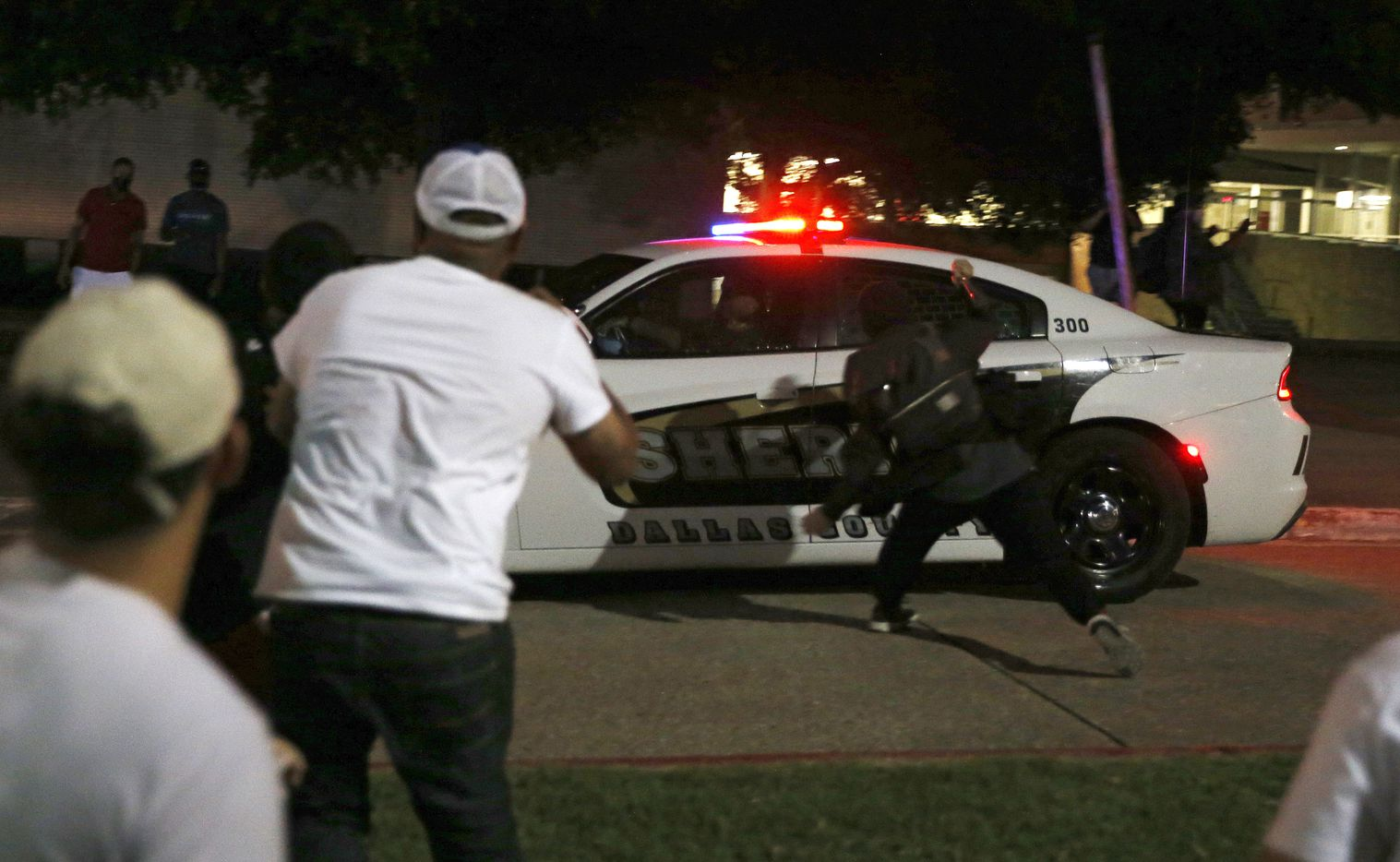 Protesters hit a Dallas County Sheriff's vehicle during a demonstration against police brutality in downtown Dallas, on Friday, May 29, 2020. George Floyd died in police custody in Minneapolis on May 25.