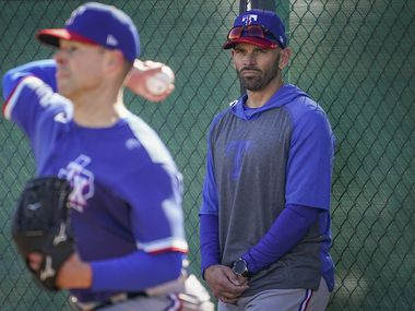 Texas Rangers pitcher Corey Kluber throws in the bullpen as manager Chris Woodward looks on during the first spring training workout for pitchers and catchers at the team's training facility on Wednesday, Feb. 12, 2020, in Surprise, Ariz.