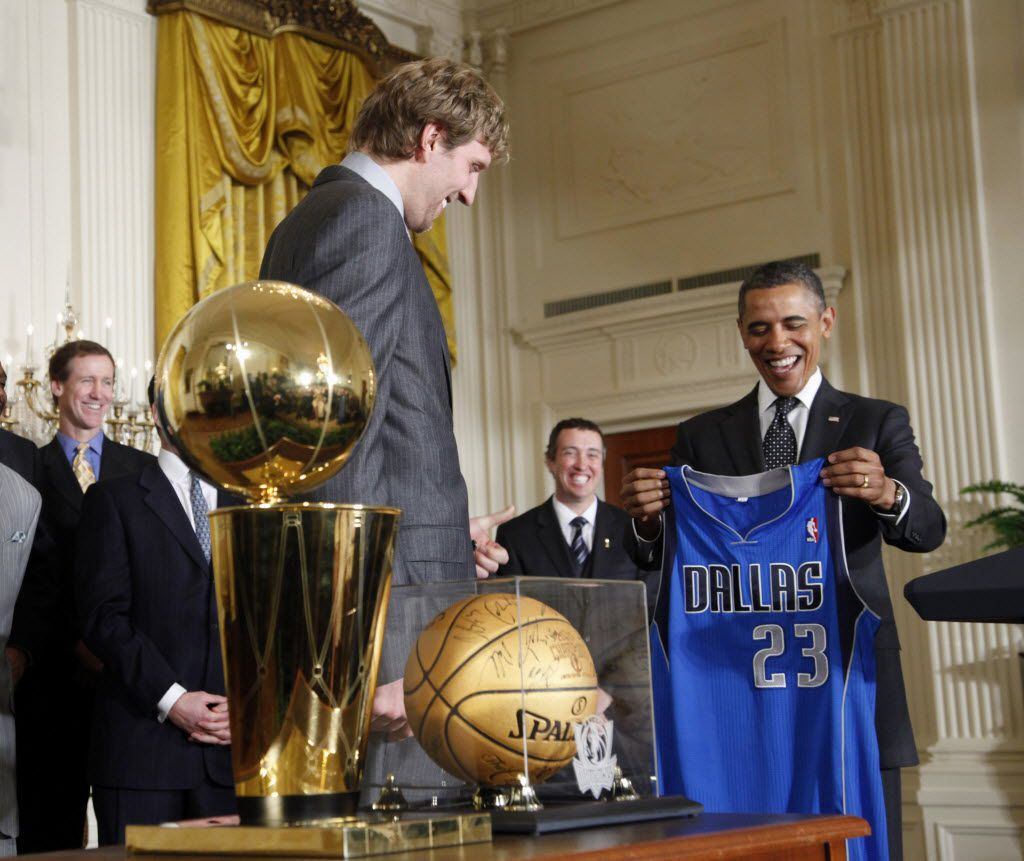 President Barack Obama is presented with a Dallas Mavericks team basketball jersey from Dirk Nowitzki as he honored the 2011 NBA basketball champions Dallas Mavericks, Monday, Jan., 9, 2012, in the East Room of the White House in Washington. (AP Photo/Pablo Martinez Monsivais)